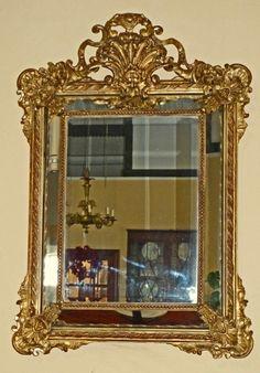 Espejo de estilo Español Colonial, enmarcación biselada con 4 paneles de espejos en los 4 costados, y realizado en dorado sobre  composición de escayola de Paris, sobre madera tallada.