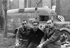Hans Kahle and Richard (surname unknown), senior commanders of the Thaelmann Battalion pose for the camera with a Spaniard. This battalion consisted of German soldiers fighting with the International Brigade against Franco and the Nationalists. They are sitting in front of a van/ambulance-type vehicle. On the side of this vehicle are the words: 'Regimiento de Acer...' and 'Cultura Popula...', along with the remains of various posters.