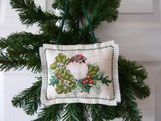 Bird and Holly cross stitched Christmas Ornament - I like the way this piece is finished: backed with the same material with a cross stitched border on both sides, polyester fiberfill stuffing, and fringed edges.
