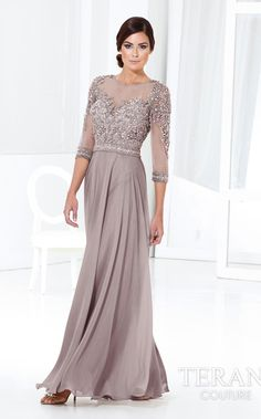 This sheerly lovely evening gown by Terani M3810 drapes you in dazzling élan. The sheer-layered bodice features crystal-embroidered shoulders and banded,