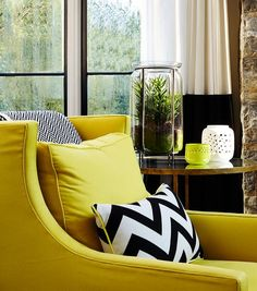 Contemporary living room features a yellow wingback chair lined with a black and white chevron pillow and a black and white herringbone throw blanket placed next to a round glass and brass end table.