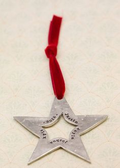 """molded star ornament  This sweet star is the perfect touch to make your holiday even more heartfelt. Each ornament is cast in fine pewter and strung with gorgeous velvet ribbon. Star measures 3"""" long not including ribbon. Customize with up to five words or names—stunning!   $28.00"""