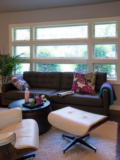 A trio of stacked windows spread natural light into this contemporary living room. A brown tufted sofa is decorated with floral throw pillows adding beautiful pink hues to the neutral room. A shag rugs adds nice depth to the smooth surfaces of the round coffee table and white leather ottoman with matching chair.