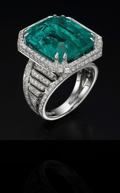 YanushGioielli   jewelry  white gold ring with diamonds, center stone is emerald.