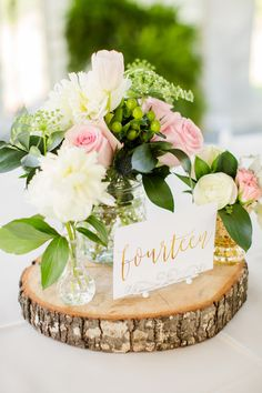 Reception centerpieces featured arrangements of dahlias, roses, tulips, ranunculuses, and greenery in pastel shades, set atop wood slices. The gold table numbers were hand-calligraphed.   	Venue: Amber Grove  	Floral Design: The...