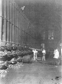 De fabricage van steenkoolgaslicht begint: arbeiders van de Gemeentelijke Gasfabriek van Rotterdam laden de retorten van de gasoven met steenkool (ca. 1890).
