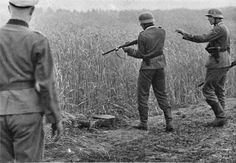 ca. 1941, USSR --- German soldiers stand over the body of a captured Russian sniper who tried to escape through wheatfields. Eastern Front, 1941. --- Image by © Hulton-Deutsch Collection/CORBIS