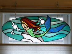 This is a stained glass panel of a mermaid looking out over the ocean.  Measures: 21 W x 8 H oval  I would also be happy to make a custom piece