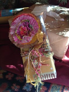 Gift wrap using Newspaper ad, embellished flower from paper scraps and ribbon remnants by Claire.