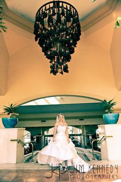 Bride under beautiful chandelier at the Waterfront Beach Resort Hilton in Huntington Beach | Jim Kennedy Photographers