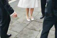 Braut umringt von Bräutigam und Trauzeugen. Hochzeitsreportage Alte Versteigerungshalle Köln.
