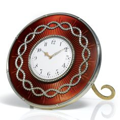 An Imperial Fabergé silver and enamel clock, workmaster Michael Perchin, St. Petersburg, circa 1901, circular, the ground enameled in translucent red over sunburst engine-turning and applied with a ring of entwined laurel, bound reed border, the aperture framed in seed pearls. Presented by Emperor Nicholas II and Empress Alexandra to their cousin, William II, German Emperor and King of Prussia, in 1901, the invoice showing the Empress' household billed for half the price.