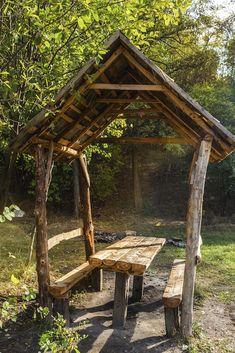 Dieser kleine Pavillon ist gebaut aus Rohholz und Schnittholz gefunden. Die Bänke sind in den Seiten des Pavillons mit einer Tabelle in der Mitte eingebaut. Dieser Pavillon ist nur groß genug, um die wenigen Menschen, die hier sitzen zu decken, aber das ist so groß wie es sein muss. Dies ist ein großer Pavillon-Tabelle auf Natur zurückgekommen.
