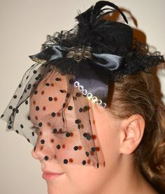 Handmade Vintage Style Black Cabaret Mini Hat with Crystal Rhinestones, Antique Silver Flower Embellishment, Polka Dot Veil, Silk Bow, Lace Trim, Satin Ribbon    Features:  Around the brim of the hat is a beautiful silk and lace trim, just above it, around the back is a small silver trim of satin ribbon for a nice contrast of color between the trim and the hat.     In the front is a silk bow lined with crystal rhinestones, and a short black polka dot veil.  In the center of the bow is an…