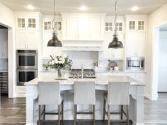 """Walls are Sherwin Williams SW 7015 Repose Gray, white cabinet color is SW Pure White, countertop is Superwhite Quartzite, single bowl stainless sink, double oven, microwave placement, cabinets to ceiling, glass top Shaker style cabinets, white 3 x 6 marble tile backsplash, wood and doors on hood, 98"""" island"""