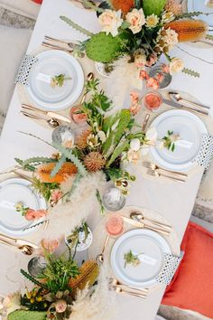Bird's eye view of full table set up for a dinner party in warm hues of cream, peach and rose gold, and three centerpieces