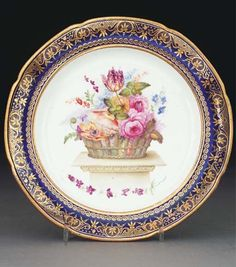 A Swansea blue-ground plate from the Lysaght service CIRCA 1820 Attributed to Henry Morris, painted with a generous basket of flowers on a marble plinth above a band of flowers, the border gilt with a band of scrolls reserved with diaper, speckle and cross-pattern sections (minor scratches and light rubbing to gilding) 9 3/8 in. (23.8 cm.) diam.