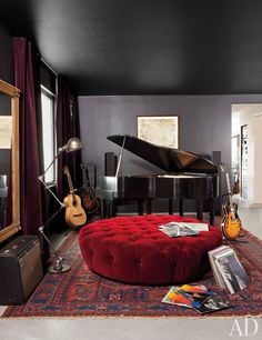 One end of the master bedroom includes a Wurlitzer baby grand piano, a custom-made ottoman, and a work on paper by Ed Ruscha.