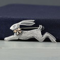 running hare with rose gold bow silver brooch by nick hubbard
