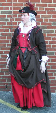 This is one of the outfits (minus hat; I usually wear my straw hat) I wear to Jamestown when I'm interpreting.  It was originally made in 2000/1 (I don't remember exactly), and is brown wool with hand-dyed linen tape trim.    The doublet is hand finished with red linen thread.  The doublet is extremely high waisted in the back to reflect the late 1500s/ early 1600s period.  The buttons are wrapped red wool over a (plastic - I couldn't find wood beads small enough) base, and the buttonholes…