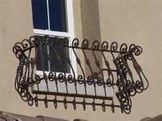 wrought iron window boxes - this is the year to do this!!! i like the curlies on top and bottom