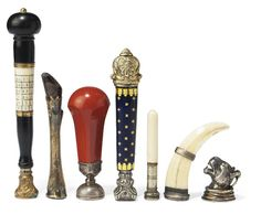 SEVEN NOVELTY DESK SEALS  SECOND HALF 19TH CENTURY  Including a silver and enamel seal, an ivory mounted seal engraved with a perpetual calendar with sectional stem revealing sharp tools, a silver seal with handle modelled as a wild-cat, a seal modelled as a deer hoof, and three further with silver or hard stone matrices. Image Christies