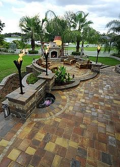This gorgeous #backyard includes water features, an outdoor #fireplace and torches.