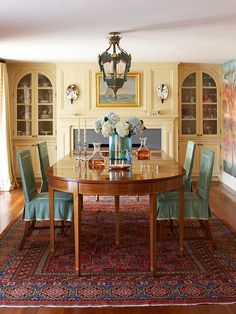 Beautiful Color Scheme  Golden Yellow + Blue + Rust  A paint technique using several layers of slightly different yellow hues finished with an antiquing glaze gives warmth to this newly renovated dining room. Chairs covered in a flirty China blue surround the table. The royal-blue-and-rust patterned antique rug introduces new colors into the warm palette.