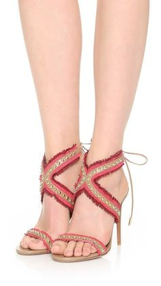 Two-tone fringe trims the studded straps on these glamorous Aquazzura sandals. Slim ties close the heel. Covered stiletto heel. Leather sole.