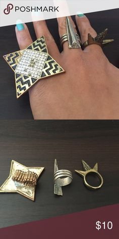 Straight edge ring bundle. One shiruken style ring (a few bling missing). Middle ring that comes to a point is closer to silver. Third ring has 3 spikes perpendicular to the finger when worn. Price is for all 3. Not of brand- branded for views. Nasty Gal Jewelry Rings