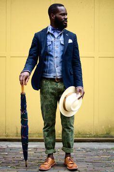 Acheter la tenue sur Lookastic: https://lookastic.fr/mode-homme/tenues/veste-en-jean-blazer--pantalon-chino-chaussures-derby-chapeau-noeud-papillon--ceinture/4871 — Nœud papillon á pois bleu marine et blanc — Chemise à manches longues bleu clair — Pochette de costume blanc — Veste en jean bleu clair — Blazer bleu marine — Ceinture en cuir brun — Chapeau en laine beige — Pantalon chino camouflage vert — Chaussures derby en cuir brunes