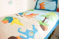 Dinosaur Quilt and Pillowsham    The lovely dinosaur range makes a lovely addition to the bedroom of a dinosaur lover or little explorer. This kids quilt and pillowsham set is colourful and vibrant featuring a colourful T-Rex and other dinosaurs in a prehistoric scene, with trees and rocks. A deep blue border and striped trim surrounds both the kids bedspread and pillowsham. | Childrens Bed Centres | Childrens Bed Centres