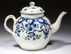 "ENGLISH CREAMWARE CERAMIC TEAPOT,  having chinoiserie underglaze blue decorations on one side and floral decorations on the other, molded twisted handles and molded spout. Incised ""TH"" on base, otherwise unmarked. Staffordshire and other areas."