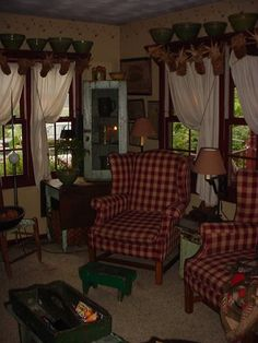 I am so doing this in my living room! Plaid chairs, sweeping curtains, shelving above the windows-all of it!