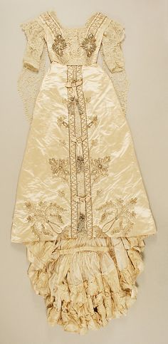 """Embroidered silk satin wedding dress with cotton lace, plastic sequins, and glass beads, American, 1907. Label: """"Fox / Paris - New York"""". Worn with net veil with wax flower head-piece."""