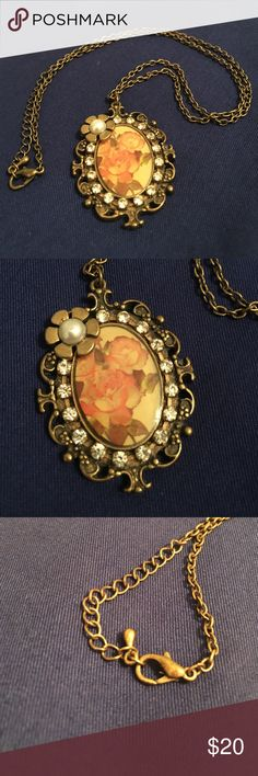 "Floral Antique Vintage Necklace  Oval flower drawing surrounded by rhinestones. At the top left a gold flower with a faux pearl in the middle. Almost reminds me of a beautiful little vintage picture frame to wear around you neck. Chain is roughly 10.5"" long. Jewelry Necklaces"