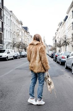 Elien Migalski wearing faux fur coat from ASOS, cashmere sweater by Zara and beige Balenciaga City Bag on the streets of Antwerp
