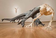 amazing wood sculpture, taking natural tree bark & extending into skeletal body standing on roots...by Javier Perez