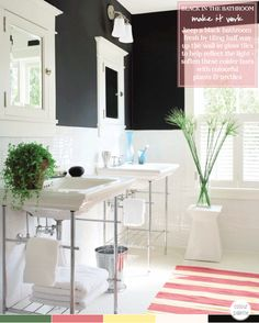 Even with the black walls, the glossy white of the tiles and sinks keeps this room light