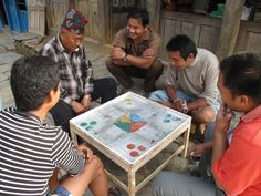 A group of men in Bandipur playing a board game. These games are very popular in Nepal.