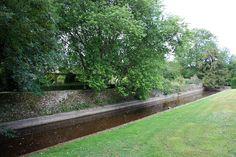 Les Jardins d'Argences - luciul apei marginit de zidul de piatra pe de o parte si de peluza tusa scurt de alta