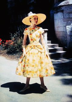 Audrey Hepburn on location for Funny Face in 1956 in a perfectly accessorised yellow print dress