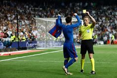Barcelona's Argentinian forward Lionel Messi (L) is shown a yellow card by referee during the Spanish league Clasico football match Real Madrid CF vs FC Barcelona at the Santiago Bernabeu stadium in Madrid on April 23, 2017. / AFP PHOTO / OSCAR DEL POZO