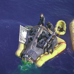 (March 16, 1966) Astronauts Neil A. Armstrong and David R. Scott sit with their spacecraft hatches open while awaiting the arrival of the recovery ship, the USS Leonard F. Mason after the successful completion of their Gemini VIII mission. They are assisted by U.S. Navy divers. The overhead view shows the Gemini 8 spacecraft with the yellow flotation collar attached to stabilize the spacecraft in choppy seas. The green marker dye is highly visible from the air and is used as a locating aid.