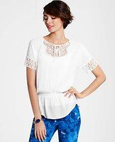 Embroidered Tunic - Channel an edgy-meets-feminine look with this alluring tunic, artfully detailed with cutout embroidery and a cinched-waist silhouette. Jewel neck with ties. Short dolman sleeves. Elasticized waist. Shirttail hem.