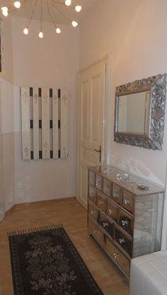 Hned při vstupu do bytu zaujme návštěvu dřevěná komoda s hliníkovým povrchem a zrcadlo sladěné do stejného stylu.