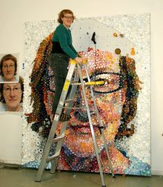 """Mary Ellen Croteau – Artist and Agitator. Working in Chicago, she created this self portrait titled, """"CLOSE"""", 8'x7' which was created from 7000 + plastic bottle caps, 2011."""