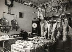 Interieur van slagerij aan de Huidenstraat in Amsterdam, met vlees op het hakblok, hangende karkassen en wat worsten. Nederland, 1917.