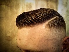 Here's a high & tight combover cut. For this style, hair is clippered short on the back and sides and then faded right out to a zero at the bottom creating a skin fade. The hair on top is then blended tightly to the sides and scissored down leaving just enough length to be combed aside. Finally, a razor part has been shaved in to complement the cut.