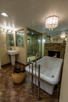 This highly textural bathroom sports distressed hardwood flooring in contrast with a large white pedestal tub, standing across from a large stone brick fireplace. Glass enclosed shower fills the entire corner space.